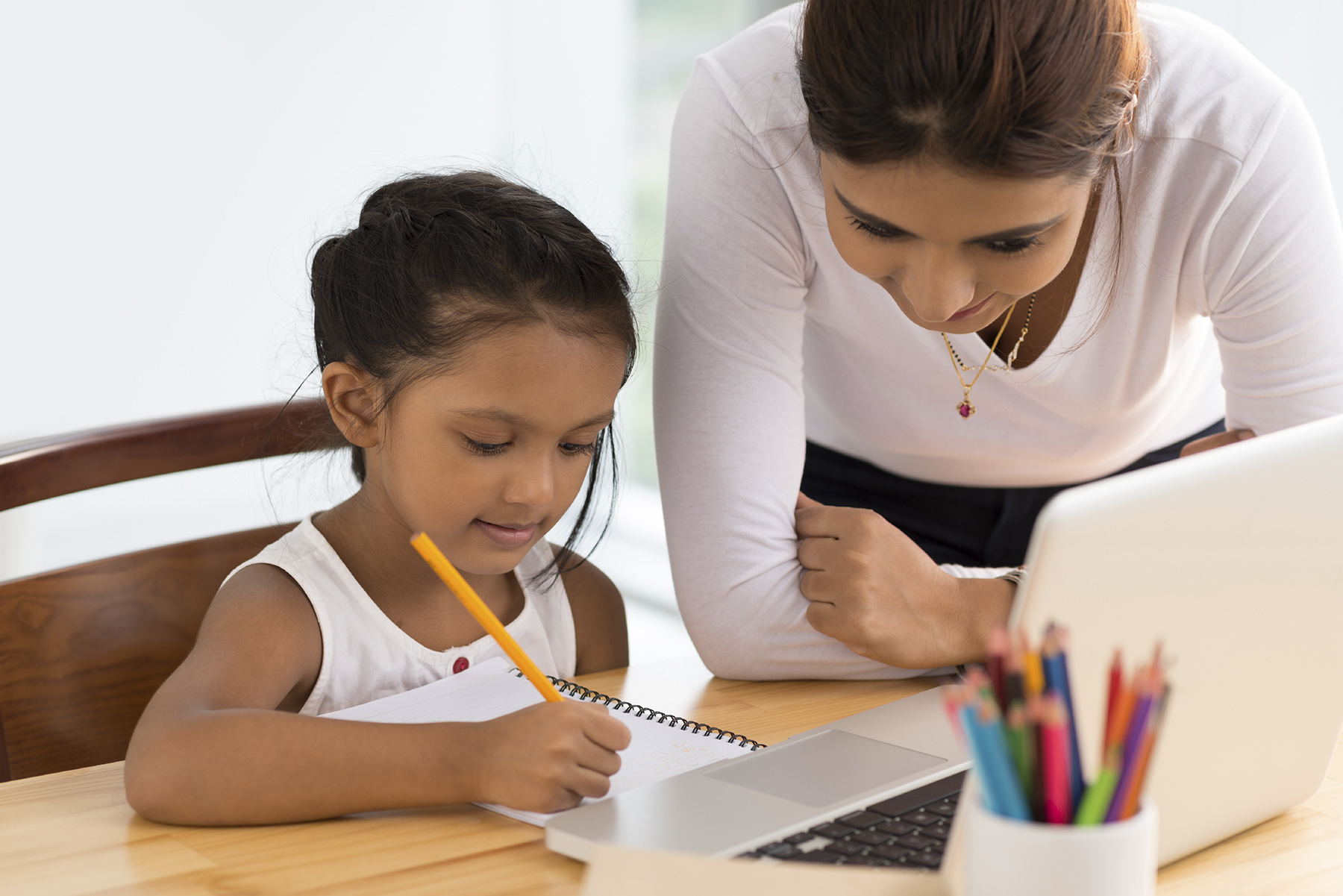 Young woman helping girl with her homework